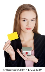 Beautiful business woman holding small house and personal card. Isolated on white.