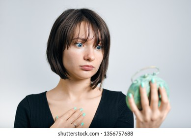 beautiful business woman is late and looks at the clock, isolated on a gray background