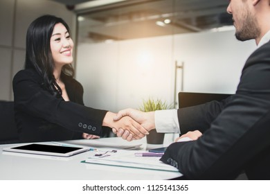 beautiful business woman making handshake with businessman, investor or partner after finishing discussion in meeting