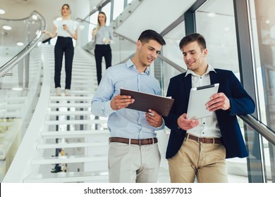 Beautiful business woman and man their holding a tablet in hands and smiling at the camera. In the background are business people.