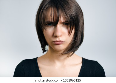 beautiful business woman is offended, isolated on gray background