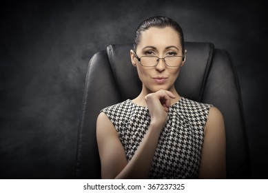 Beautiful business woman  on the black chair.