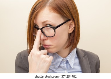Beautiful business woman with red hair and blue eyes wearing glasses.