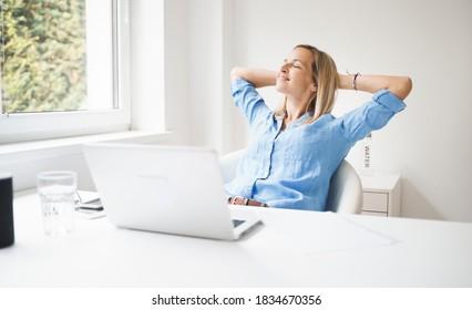schöne Geschäftsfrau entspannt sich in ihrem Heimatbüro hinter ihrem Notizbuch während der Corona-Zeit