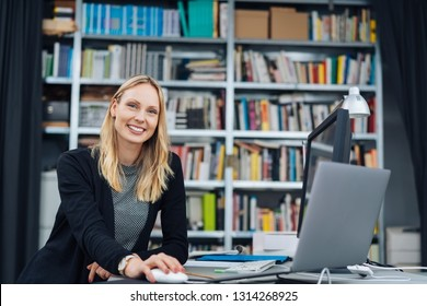 Beautiful business woman sitting at the desk and working in the office. Low angle half-length portrait