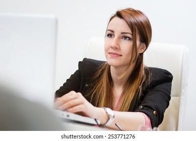 Beautiful business woman sitting in office and typing on laptop.