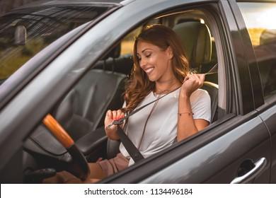 Beautiful business woman sitting on car seat and fastening seat belt.
