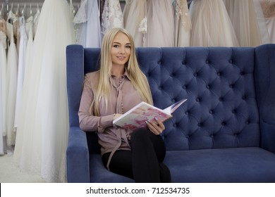 Beautiful business woman sitting on the sofa and fills her planner