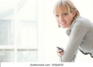 Beautiful business woman smiling and looking at camera in a modern office