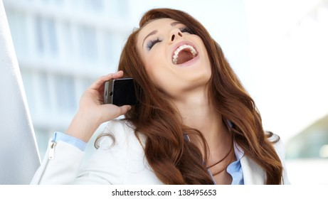 Beautiful business woman talking on cell phone while looking at copyspace
