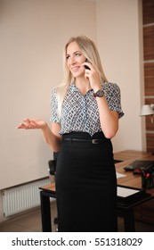 Beautiful business woman talking on mobile phone. Young female model work with sales in bright office.
