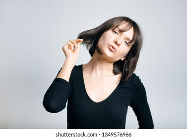 beautiful business woman touches a new hairstyle, isolated on a gray background