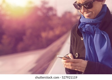 Beautiful business woman uses smart phone next to solar panels at sunset