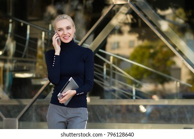 Beautiful business woman uses a tablet and speaks by phone . Student using tablet and speaks by phone in the outdoor .