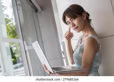 Beautiful business woman using a laptop computer. Portrait of asian.