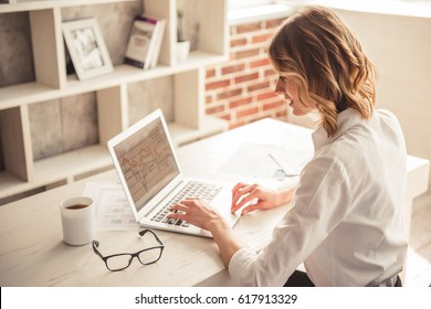 Beautiful business woman is using a laptop and smiling while working in office