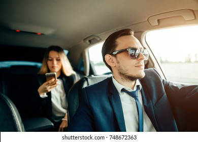 Beautiful business woman is using a smart phone and smiling while sitting on back seat in the car