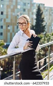 Beautiful business woman walking outside near office