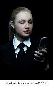 Beautiful business woman wearing black tie and jacket isolated on black background with cell phone