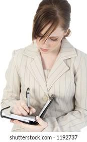 Beautiful business woman writing in datebook.