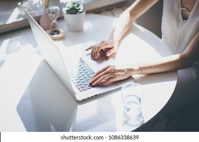 Beautiful business women pointing hand on a laptop computer while sitting at the wooden table in light coloured living room of modern house.