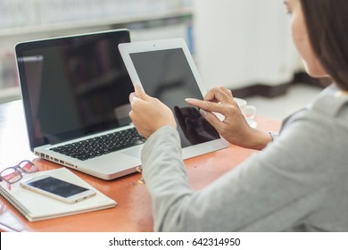 Beautiful business working woman using Ipad while working with laptop