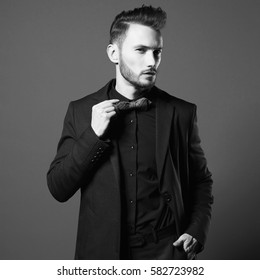 Beautiful businessman. Male beauty. Portrait of stylish man in black suit. Fashionable man. Male fashion. Portrait of elegant young man in expensive dark suit. Sexy young guy with modern hairstyle.