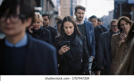 Beautiful Businesswoman in Black Coat is Using a Smartphone on a Street in Downtown. She Walks on a Crowded Pedestrian Street and Looks Successful. She's Browsing the Web on Her Device.