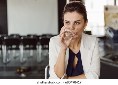Beautiful businesswoman at the co-working drinks water. Blurred background. Film effect. Open space