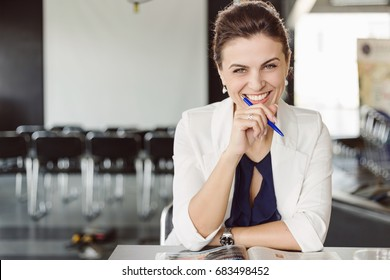 Beautiful businesswoman at the co-working smiling. Blurred background. Film effect. Open space