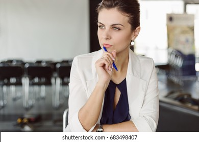 Beautiful businesswoman at the co-working thinking. Blurred background. Film effect. Open space