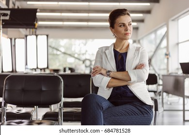 Beautiful businesswoman at the co-working is thinking. Blurred background. Film effect. Open space