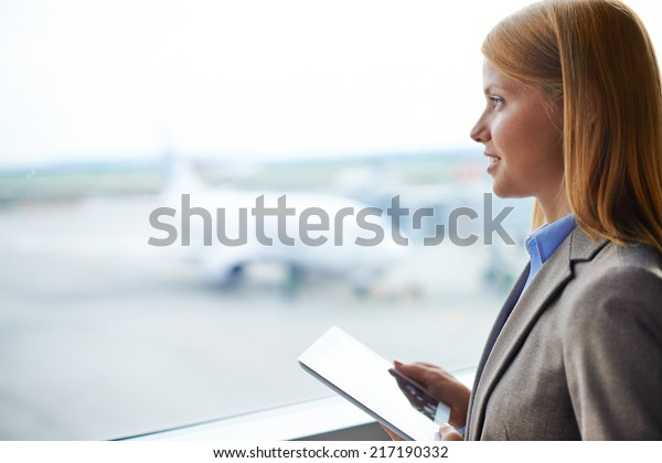 Beautiful businesswoman with digital tablet looking through window in airport