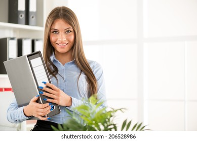 Beautiful Businesswoman with documents standing in the office and looking at camera.