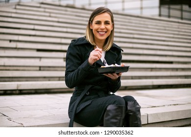 Beautiful businesswoman enjoys resting on a lunch break while sitting on the staircase in the city.Toned image.