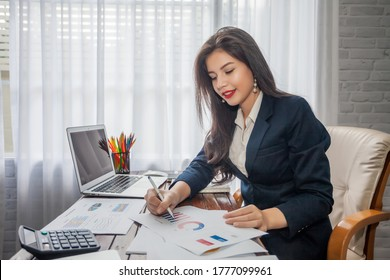 Beautiful businesswoman or financial manager working in modern office on a laptop.