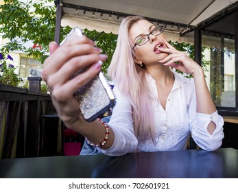 Beautiful businesswoman in glasses taking a selfie in a cafe.