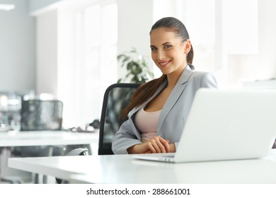 Beautiful Businesswoman in Her Office working on Laptop Computer