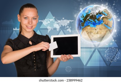 Beautiful businesswoman holding blank tablet PC and blank business card in front of PC screen. Globe, world map, network with people icons, triangles and other virtual elements as backdrop. Elements