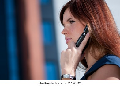 Beautiful businesswoman make call by mobile cell phone. Outdoor, over city.