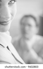 Beautiful businesswoman and man look off in same direction with woman's face up close and man's face blurred in the background