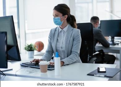 Schöne Geschäftsfrau mit medizinischer Maske, die im Büro arbeitet. Covid-19 Konzept.