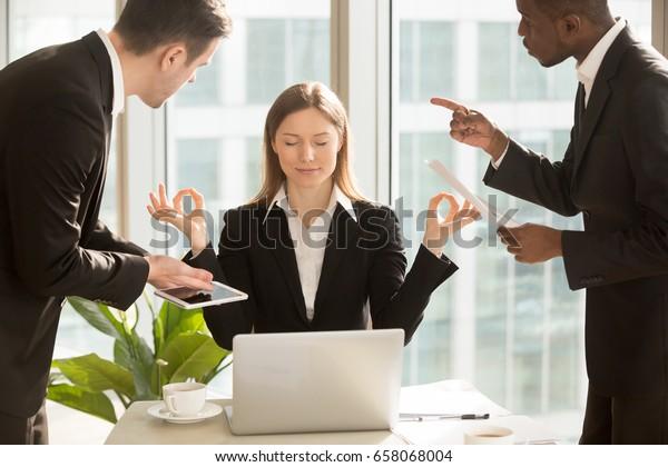 Красивая деловая женщина медитирует на рабочем месте, игнорируя работу, не слушая раздражающих клиентов или беспокоящих коллег, разговаривающих с ней, сидя за офисным столом с закрытыми глазами, сохраняйте спокойствие, без стресса