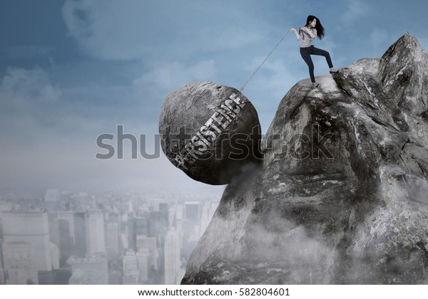 Beautiful businesswoman pulls big rock with persistence word while climbing on the cliff