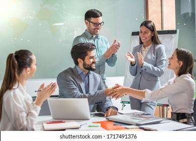 Schöne Geschäftsfrau schüttert Händchen mit Geschäftsmännern, während ihre Kollegen Händklatschen und erfolgreiche Geschäftspartnerschaft im Büro feiern