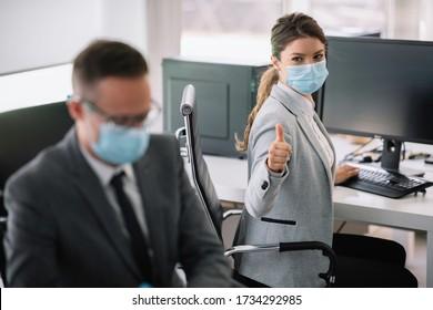 Schöne Geschäftsfrau zeigt Daumen auf. Geschäftsfrau mit medizinischer Maske.