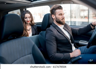 Beautiful businesswoman sitting on the backseat with elegant man driving the car in the city