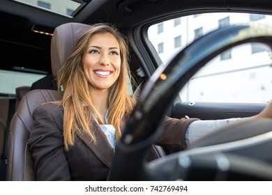 Beautiful businesswoman smiling in a car view form steering wheel