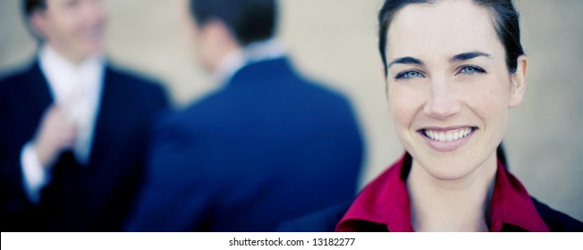 beautiful businesswoman standing and smiling while two businessmen talk in the background