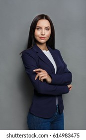 Beautiful businesswoman studio shot on grey background. Charming and confident serious brunette woman in casual dark blue jacket